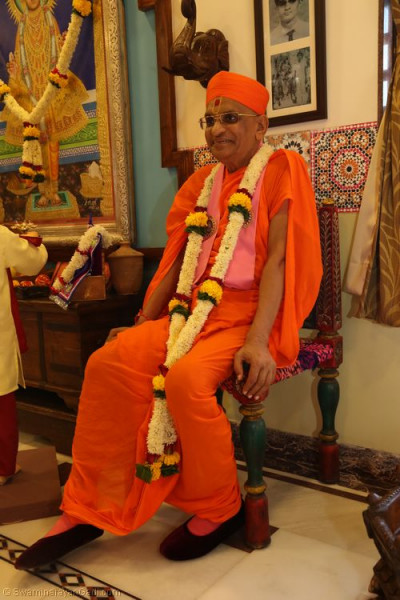 His Divine Holiness Acharya Swamishree sits on one of the chairs
