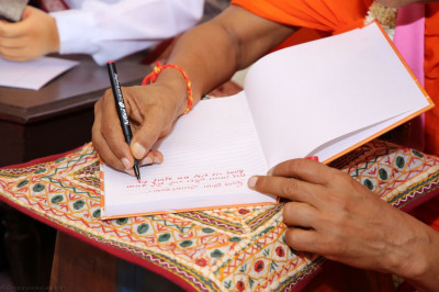 Divine darshan of Acharya Swamishree writing a prayer
