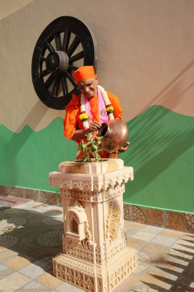 Divine darshan of Acharya Swamishree holding a karsh and watering a plant