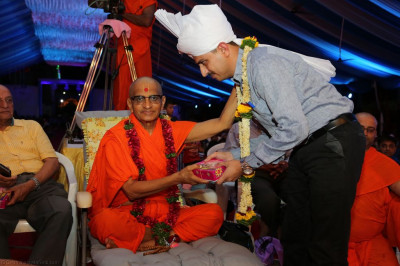 His Divine Holiness Acharya Swamishree presents a garland of fresh flowers, a paag and prasad to the honoured guest