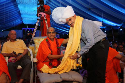 His Divine Holiness Acharya Swamishree presents a garland of fresh flowers, a paag, a shawl and prasad to the honoured guest