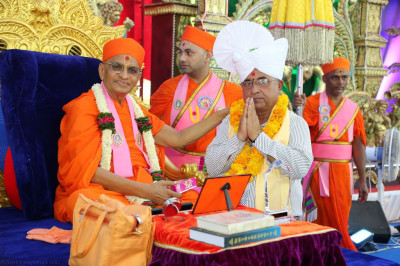 His Divine Holiness Acharya Swamishree presents a prasad paag, a shawl and a garland of flowers to the honoured guest