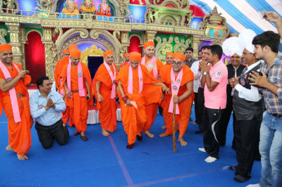 Sants escort His Divine Holiness Acharya Swamishree from the stage whilst performing a drama