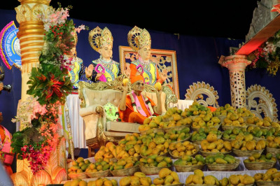 Divine darshan of His Divine Holiness Acharya Swamishree holding a mango in each lotus hand