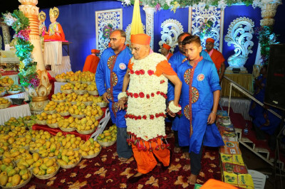 Disciples escort His Divine Holiness Acharya Swamishree to cut the cake