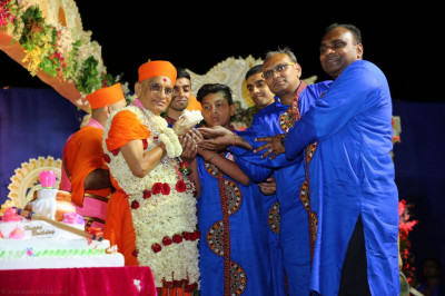 Disciples offer cake to His Divine Holiness Acharya Swamishree
