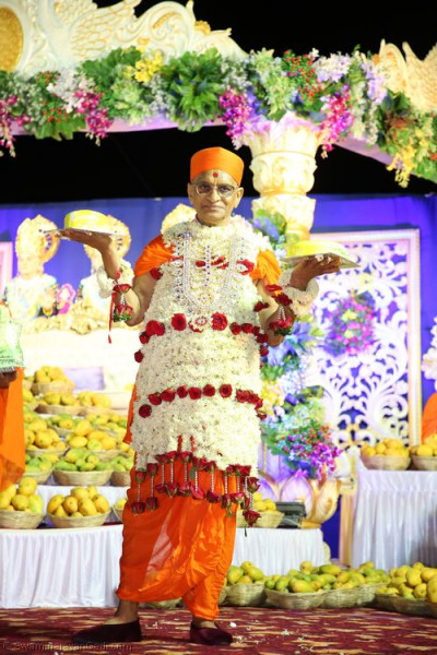 Divine darshan of Acharya Swamishree holding 2 of the cakes