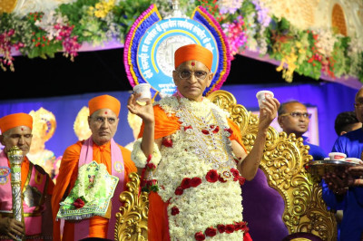 Divine darshan of His Divine Holiness Acharya Swamishree holding ice cream prasad
