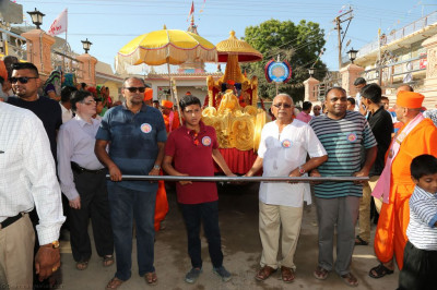 Disciples who have sponsored the day's celebrations pull the golden chariot towards the grand assembly