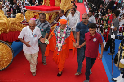 Disciples escort His Divine Holiness Acharya Swamishree onto the stage
