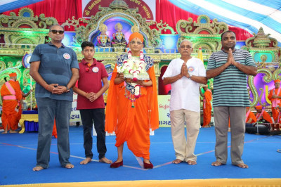 His Divine Holiness Acharya Swamishree blesses disciples on stage