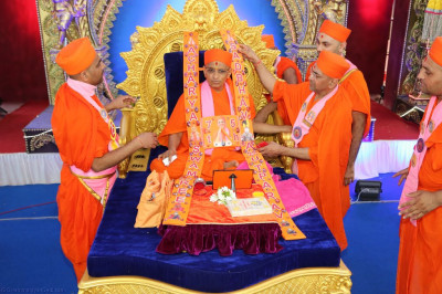 A garland is presented to Acharya Swamishree