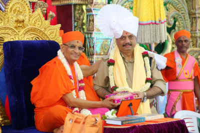 His Divine Holiness Acharya Swamishree presents a prasad paag, shawl and consecrated sweets to the honoured guest A K Jadeja - Inspector General of Police Kutch District