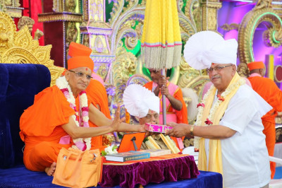 His Divine Holiness Acharya Swamishree presents a prasad paag, shawl and consecrated sweets to the honoured guest