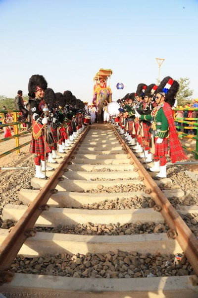His Divine Holiness Acharya Swamishree blesses Shree Muktajeevan Swamibapa Pipe Band performing 'Rel gadi chali amari' whilst standing on the rail tracks