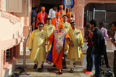 Disciples who have sponsored today's celebrations escort His Divine Holiness Acharya Swamishree from the mandir to the golden chariot