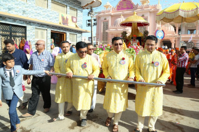 Disciples who have sponsored the day's celebrations pull the golden chariot from mandir to the grand assembly