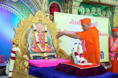 His Divine Holiness Acharya Swamishree showers fresh fragrant flower petals at the divine lotus feet of Sadguru Shree Ischwarcharandasji Swami as part of the 150th anniversary celebrations