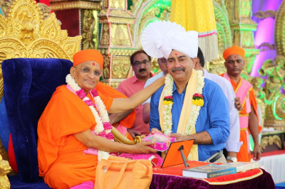 His Divine Holiness Acharya Swamishree blesses the honoured guest with a prasad paag and a garland of flowers