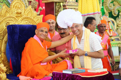 His Divine Holiness Acharya Swamishree blesses the honoured guest with a prasad paag, a shawl and a garland of flowers