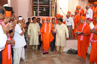 Disciples escort His Divine Holiness Acharya Swamishree through the mandir
