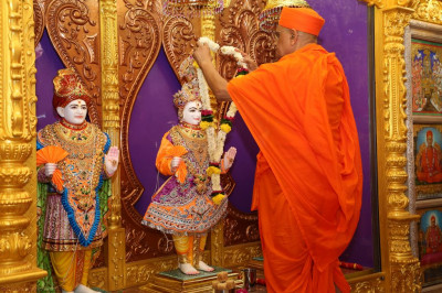 His Divine Holiness Acharya Swamishree presents a garland fresh fragrant flowers to Lord Shree Swaminarayan