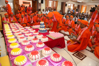 His Divine Holiness Acharya Swamishree cuts a piece of cake