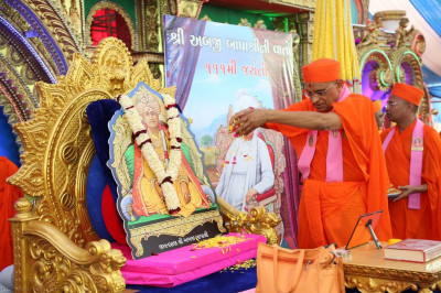 His Divine Holiness Acharya Swamishree showers flower petals at the divine lotus feet of Jeevanpran Shree Abji Bapashree