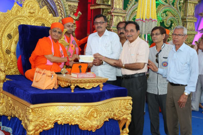 His Divine Holiness Acharya Swamishree presents cheques to local charitable organisations on behalf of Maninagar Shree Swaminarayan Gadi Sansthan