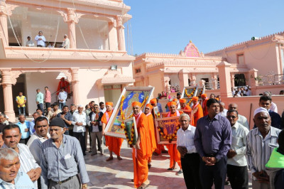 Sants carefully carry the murti from the chariot to inside the mandir