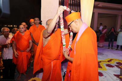 Sants present a garland of fresh flowers to His Divine Holiness Acharya Swamishree