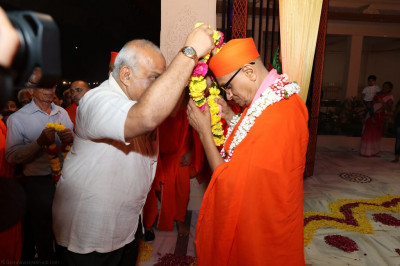 Disciples present a garland of fresh flowers to His Divine Holiness Acharya Swamishree