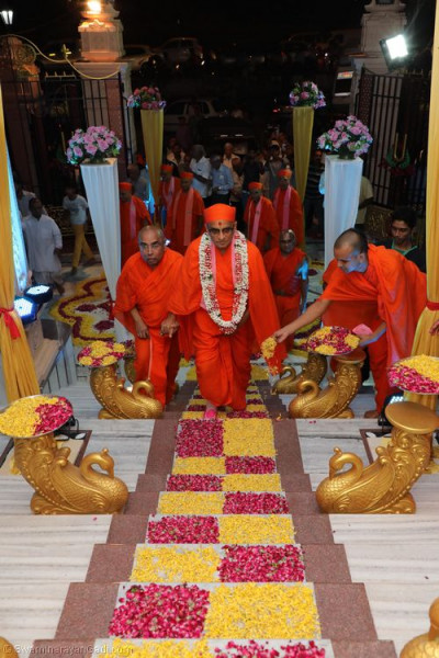 His Divine Holiness Acharya Swamishree walks up the steps decorated with fresh colourful flower petals
