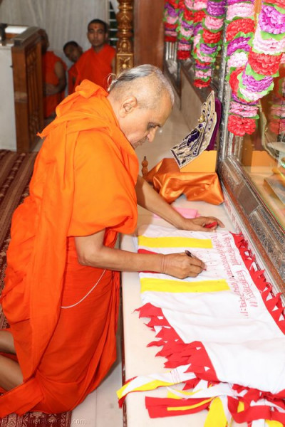 His Divine Holiness Acharya Swamishree inscribes the divine name of Lord Shree Swaminarayanbapa Swamibapa on the new mandir flags