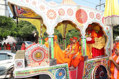 Divine darshan of His Divine Holiness Acharya Swamishree and sants seated inside the horse drawn carriage