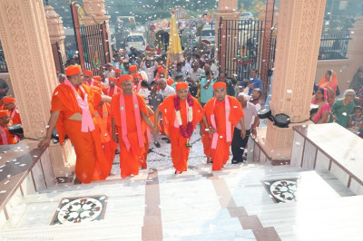 Confetti cannons shower the area as sants escort His Divine Holiness Acharya Swamishree up the mandir steps