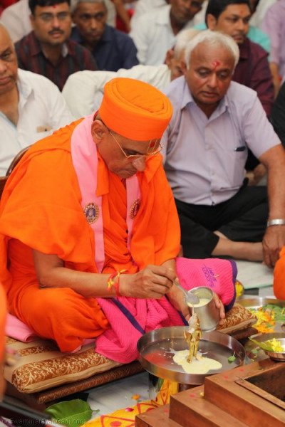 His Divine Holiness Acharya Swamishree bathes the Lord in the five nectars as part of the poojan ceremony