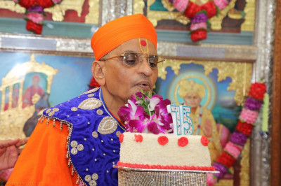 His Divine Holiness Acharya Swamishree blows out the candle on the cake