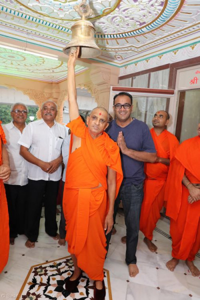 His Divine Holiness Acharya Swamishree rings the bell