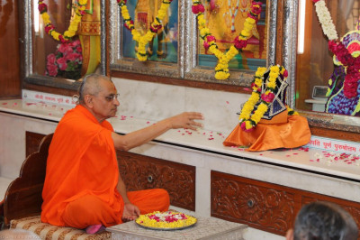 His Divine Holiness Acharya Swamishree performs the anniversary poojan ceremony and showers flower petals at the divine lotus feet of Lord Shree Swaminarayanbapa Swamibapa