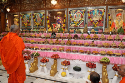 His Divine Holiness Acharya Swamishree performs aarti as the Lord dines on the magnificent annakut of sweet and savoury items