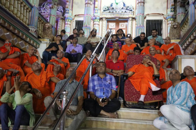 His Divine Holiness Acharya Swamishree, sants and disciples watch seated on the steps of Maninagar mandir
