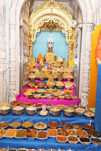 Divine darshan of Shree Harikrishna Maharaj dining on the annakut of sweet and savoury items