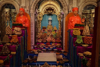 Divine darshan of Lord Shree Swaminarayan, Sadguru Shree Gopalanand Swamibapa and Sadguru Shree Nirgundasji Swamibapa dining on the magnificent annakut of sweet and savoury items