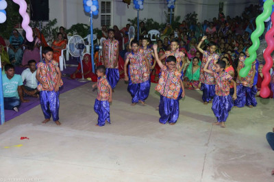 Young disciples perform a dance to a devotional song