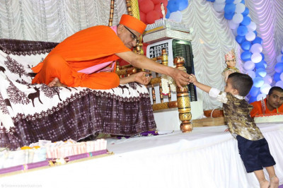 His Divine Holiness Acharya Swamishree presents prasad to a young disciple