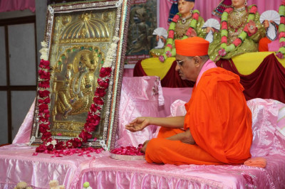 His Divine Holiness Acharya Swamishree showers flower petals at the lotus feet of Shree Sahajanand Swami