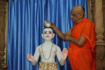 His Divine Holiness Acharya Swamishree bathes Lord Shree Swaminarayan with warm fragrant water