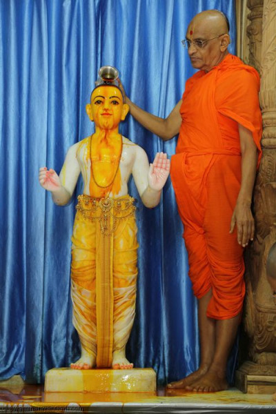 His Divine Holiness Acharya Swamishree bathes Lord Shree Swaminarayan with warm saffron water