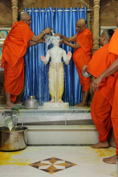 His Divine Holiness Acharya Swamishree bathes Lord Shree Swaminarayan with warm milk